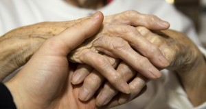 young_man_s_hand_holding_seniors_hand
