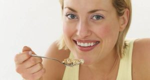 Smiling Woman Eating Cereal