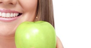 healthy smiling woman holding green apple, half face, isolated over white background